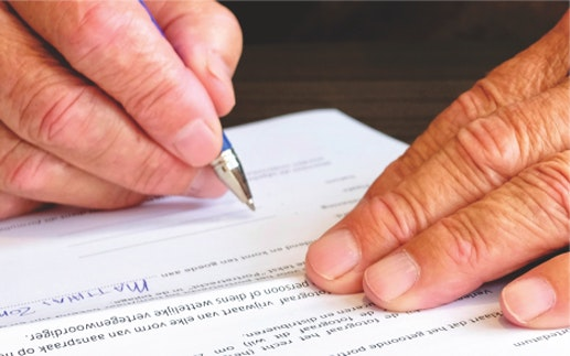 close up of someone's hands signing a document