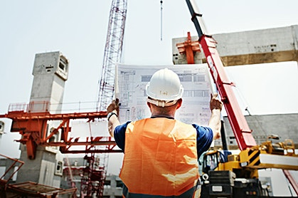 construction worker holding up a blueprint in front of a building under construction
