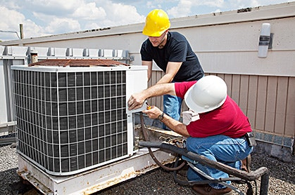 two men working on an air conditioning unit on a roof